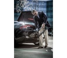 Мужчина кладет в багажник авто Электросамоката Emicro ONE черный