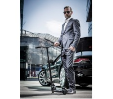 Мужчина готовится положить Электросамокатом Emicro ONE черный в багажник автомобиля