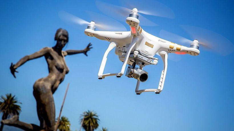 Квадрокоптер летит в небе на фоне статуи каменной девушки