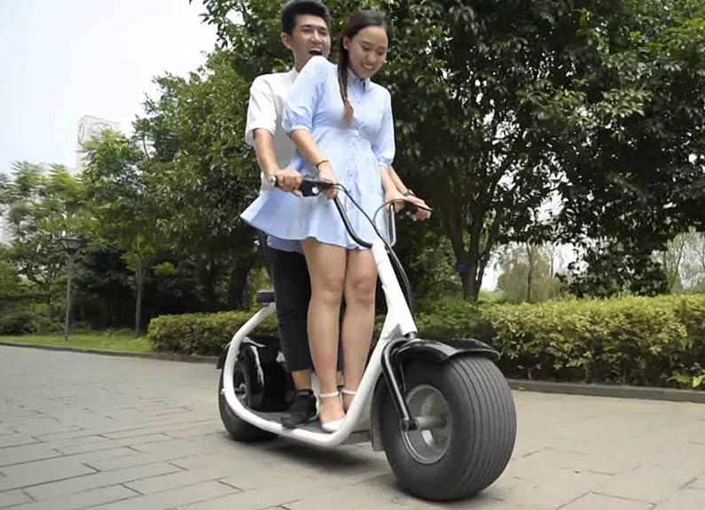 Девушка и парень на электросамокате Citycoco