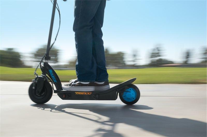 молодой человек в кедах едет на электросамокате от Razor называется он powercor e 100 синего цвета