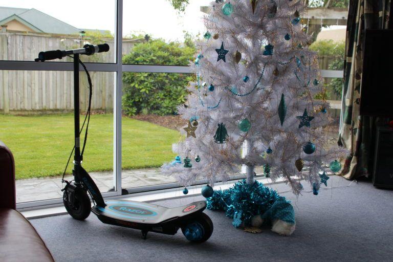 электросамокат  Razor PowerCore e100 синего цвета стоит напротив панорамного окна с елкой