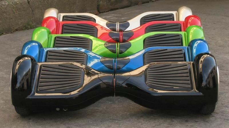 Гироскутеры с размером колес 6.5 дюймов стоят рядом. Представлены цвета: черный, синий, зеленый, красный, бежевый
